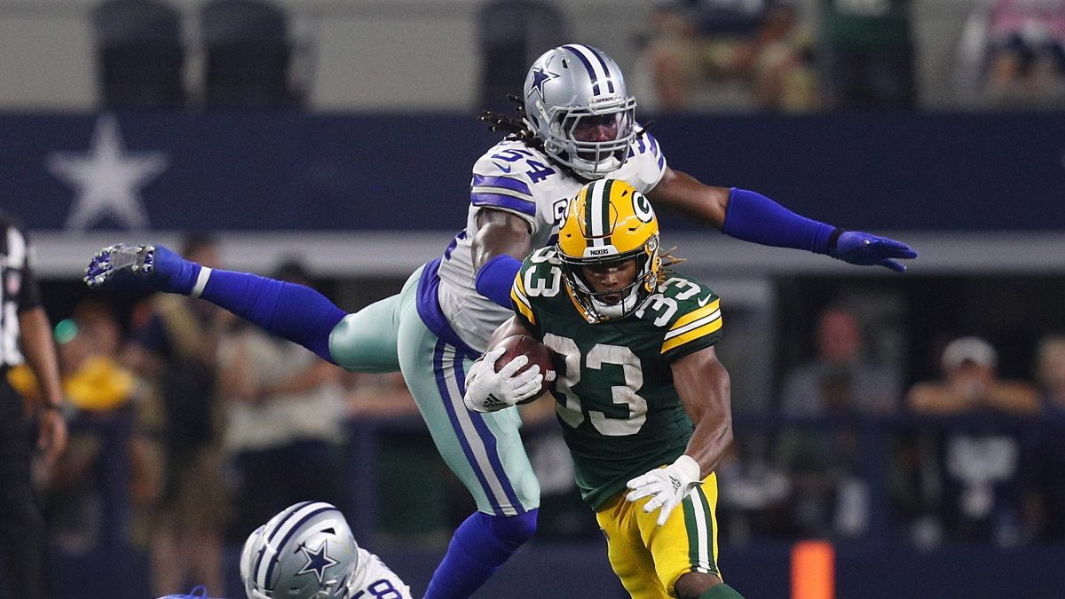 ARLINGTON, TEXAS - OCTOBER 06: Aaron Jones #33 of the Green Bay Packers evades Jaylon Smith #54 and Robert Quinn #58 of the Dallas Cowboys in the fourth quarter at AT&T Stadium on October 06, 2019 in Arlington, Texas. (Photo by Richard Rodriguez/Getty Images)
