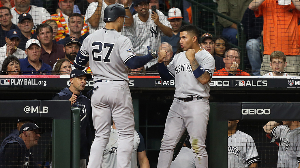 HOUSTON, TEXAS - OCTOBER 12:  Giancarlo Stanton #27 of the New York Yankees is congratulated by his teammate Gleyber Torres #25 after his solo home run against the Houston Astros during the sixth inning in game one of the American League Championship Series at Minute Maid Park on October 12, 2019 in Houston, Texas. (Photo by Bob Levey/Getty Images)